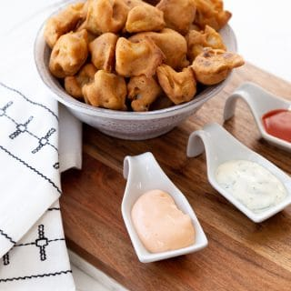 A white bowl filled with cauliflower poppers and three white appetizer spoons with dipping sauces and a black and white napkin.