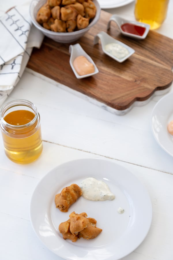 A white plate with 2 cauliflower poppers and white sauce and a glass of beer and a bowl of poppers and dipping sauces in the background.