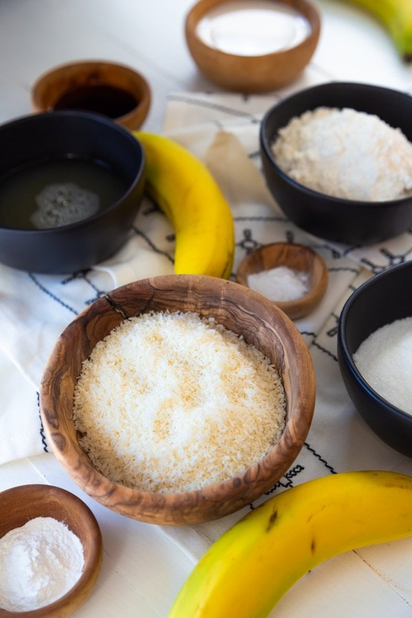 Wood bowls and black measuring cups with cake ingredients and two bananas on a white wood table.