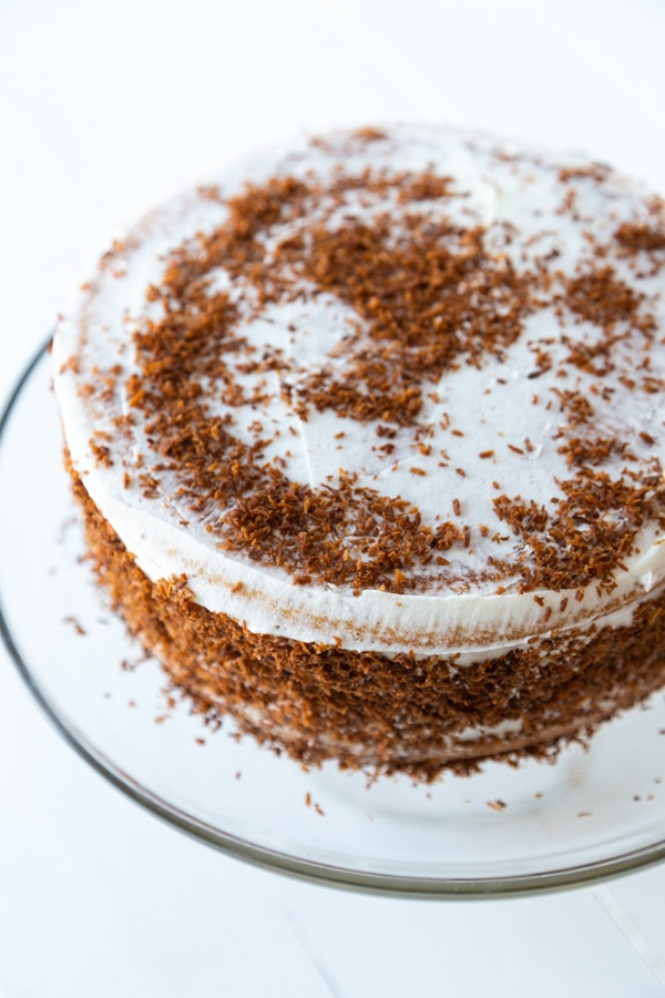 A cake with white frosting and brown sugar sprinkled on top