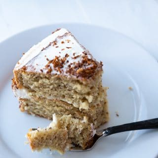 A slice of cake on a white plate with a fork and a piece of cake resting on it.