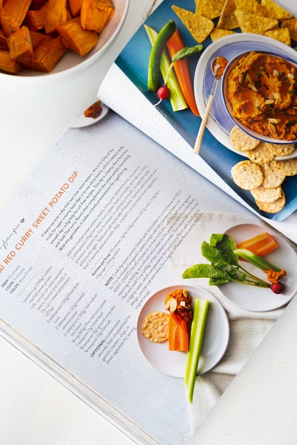 The Vegan 8 cookbook opened to the Thai Curry Dip page with a bowl of the dip in the background