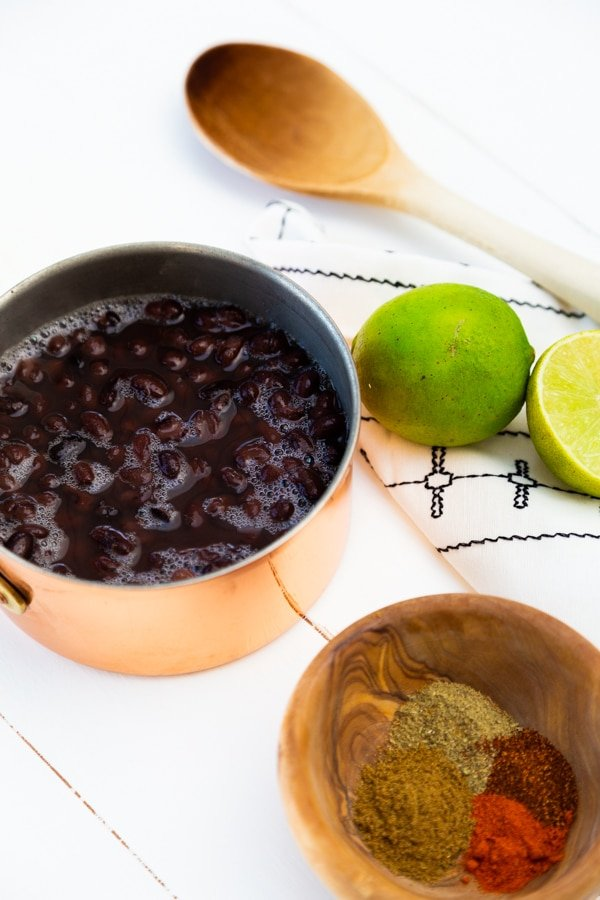 A copper pot with black beans and limes and a wood spoon next to the pot