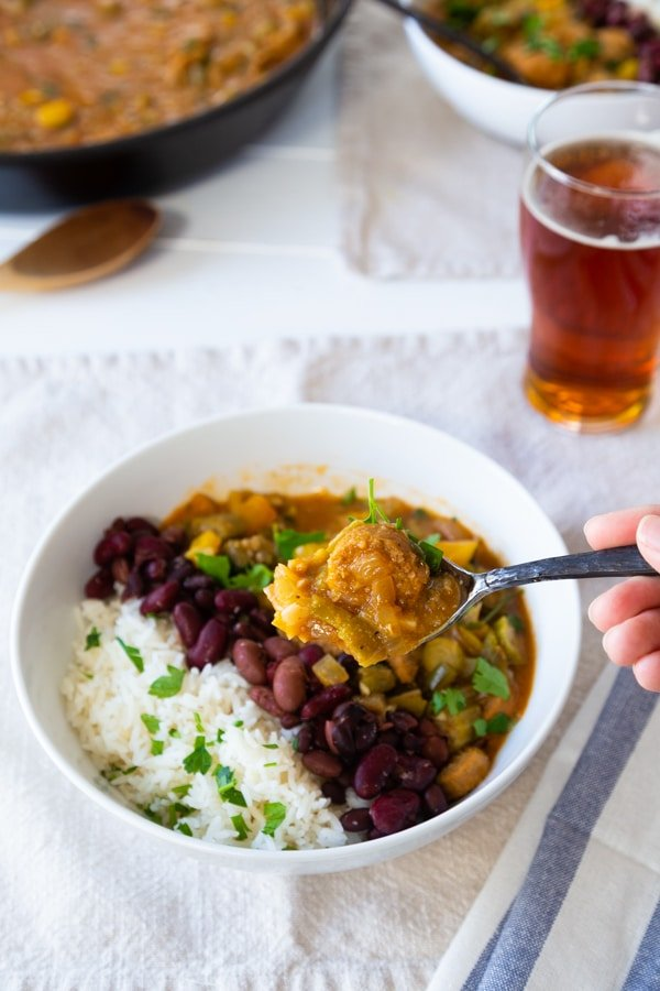 Gumbo in a white bowl with beans and rice with a hand holding a spoon of the stew, and a glass of beer and a skillet of gumbo in the background.