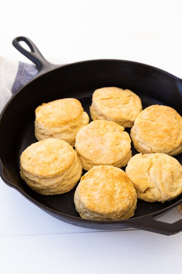 Golden brown baked biscuits in a black cast-iron skillet