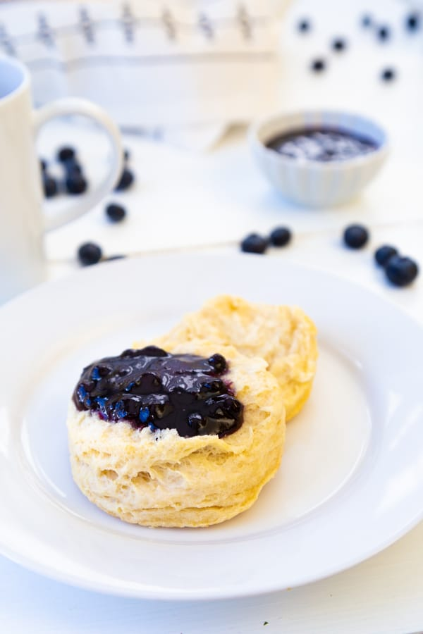 A white plate with a biscuit and blueberry preserves spread on top of it and blueberries on a white table next to the plate