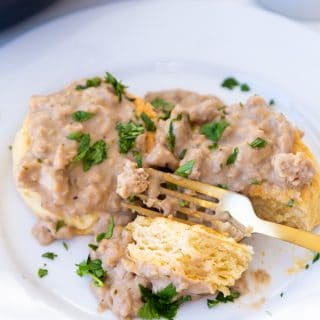 Biscuits and gravy on a white plate with a gold fork