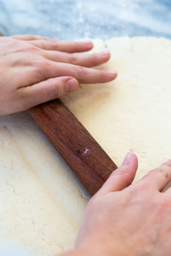 Hands rolling out dough with a wood rolling pin
