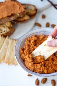 A hand dipping a cracker into a bowl of red pepper pate with crackers and almonds around the bowl on a white table.