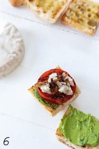An open face caprese sandwich on a white board.