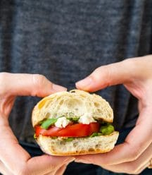 Two hands holding a caprese salad sandwich.