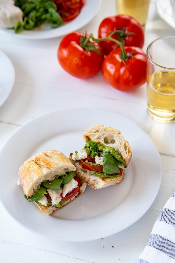 A caprese sandwich on a white plate with tomatoes and a glass of wine next to it.
