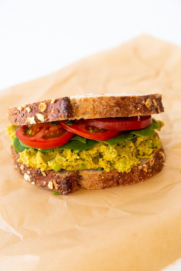 A smashed chickpea, spinach, and tomato sandwich on parchment paper.