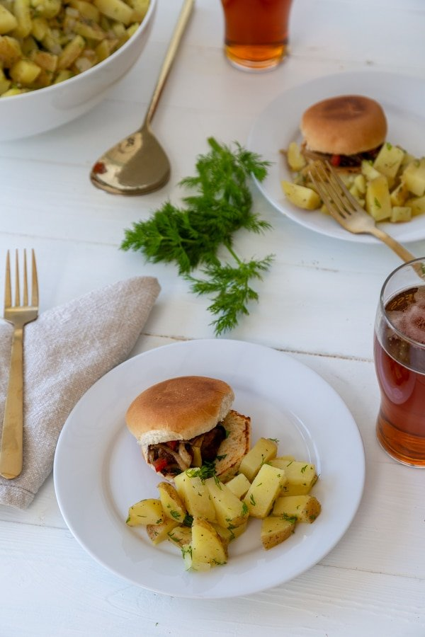 A white wood table with a white plate with a burger and potato salad and a large white bowl of potato salad, glasses of beer, and another plate of food.