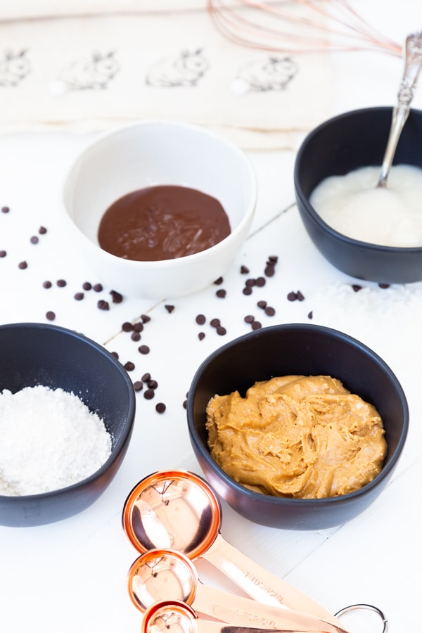 Black and white bowls with peanut butter, powdered sugar, condensed milk, and vanilla