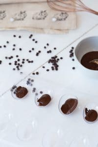 an Easter egg candy mold with a bowl of melted chocolate and chocolate chips