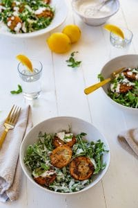 Three white bowls with salads and lemons on the table and gold utensils.