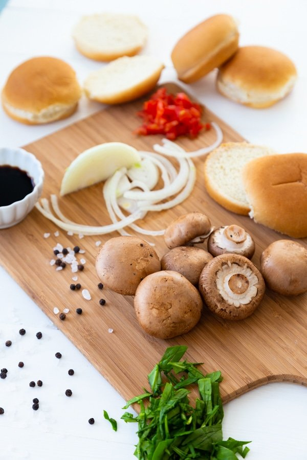 A cutting board with mushrooms, onion, and hamburger buns