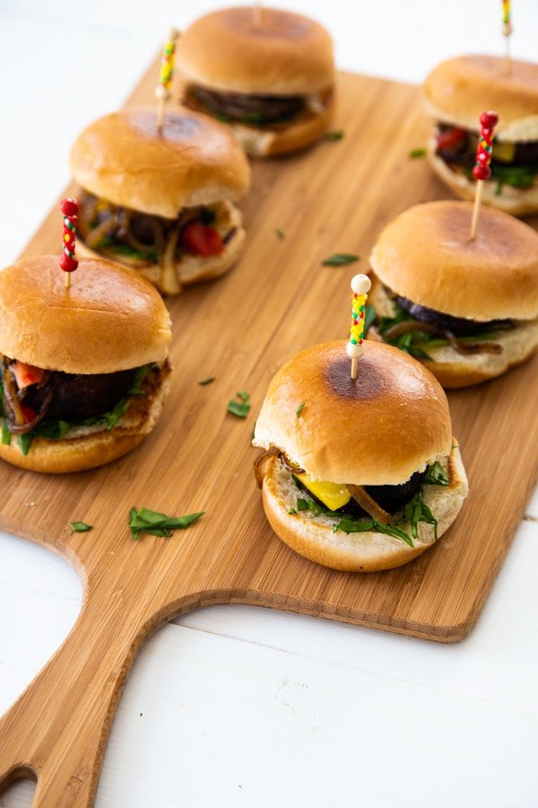 Mushroom sliders on a wood board with toothpicks in the center of the buns.