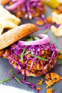 A pulled BBQ sandwich featured in the Veganosity cookbook Great Vegan BBQ Without a Grill with the bun half on the top and onions and slaw on top of the sandwich