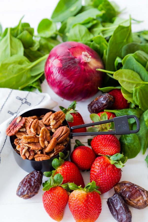 Spinach, strawberries, pecans, dates, and a red onion for salad