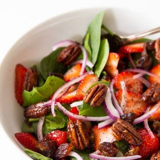 A white bowl with strawberry spinach salad and candied pecans