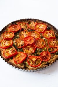 A cooked tomato and spinach tart in a tart pan