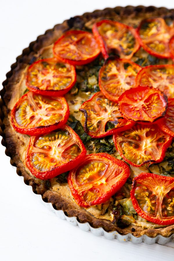 Half of a tomato tart in a tart pan on a white surface