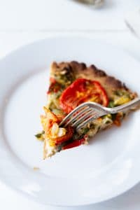 A slice of tomato tart featured on Veganosity on a white plate with a silver fork cutting into it.