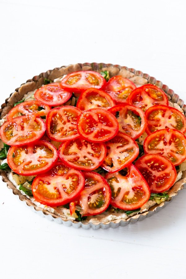 An uncooked tomato tart on a white surface