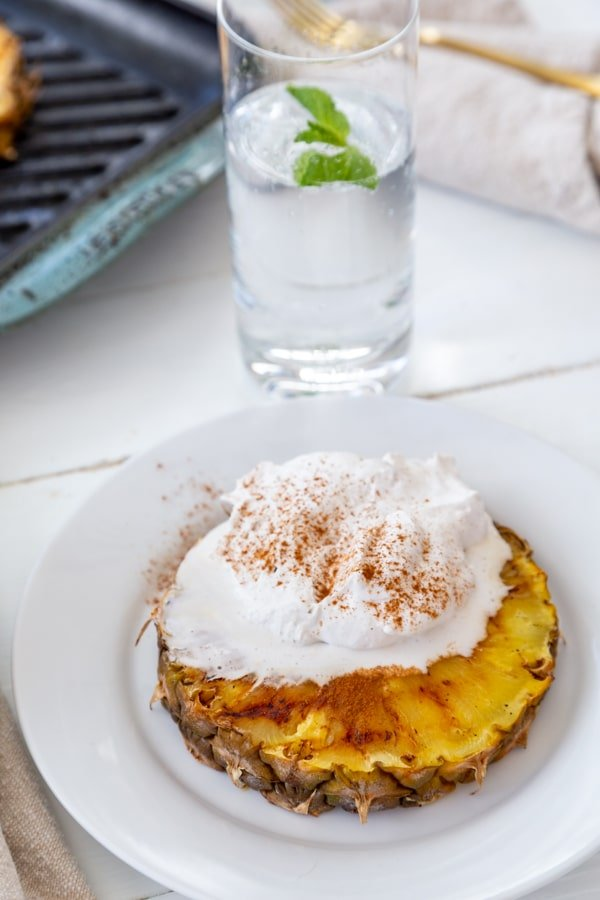 A slice of grilled pineapple with whipped cream and cinnamon on a white plate with a glass of water in the background.