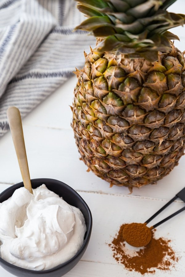 A black bowl filled with whipped cream and a gold spoon in the bowl, and a black measuring spoon with cinnamon spilling off of it and a pineapple on a white wood table.
