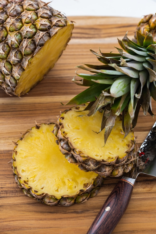 2 slices of pineapple with a knife on a wood board and the crown of the pineapple leaning on one slice an the rest of the whole pineapple in the background.