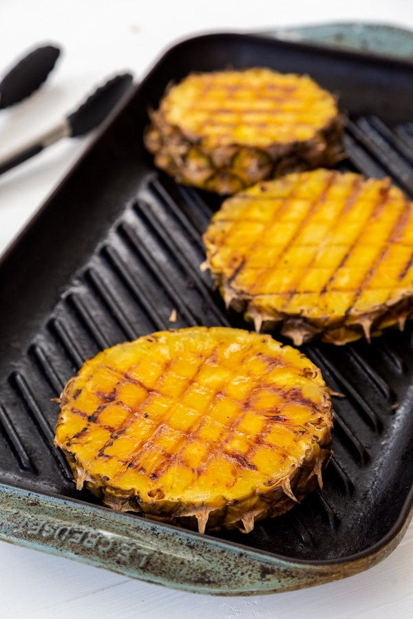 Three slices of grilled pineapple on an iron grill pan with tongs in the background.