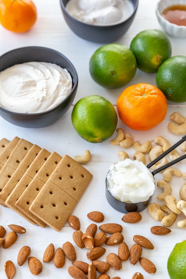 Limes, oranges, cashews, almonds, graham crackers, and two black bowls filled with cream cheese, coconut oil, and coconut milk and a white dish with maple syrup.