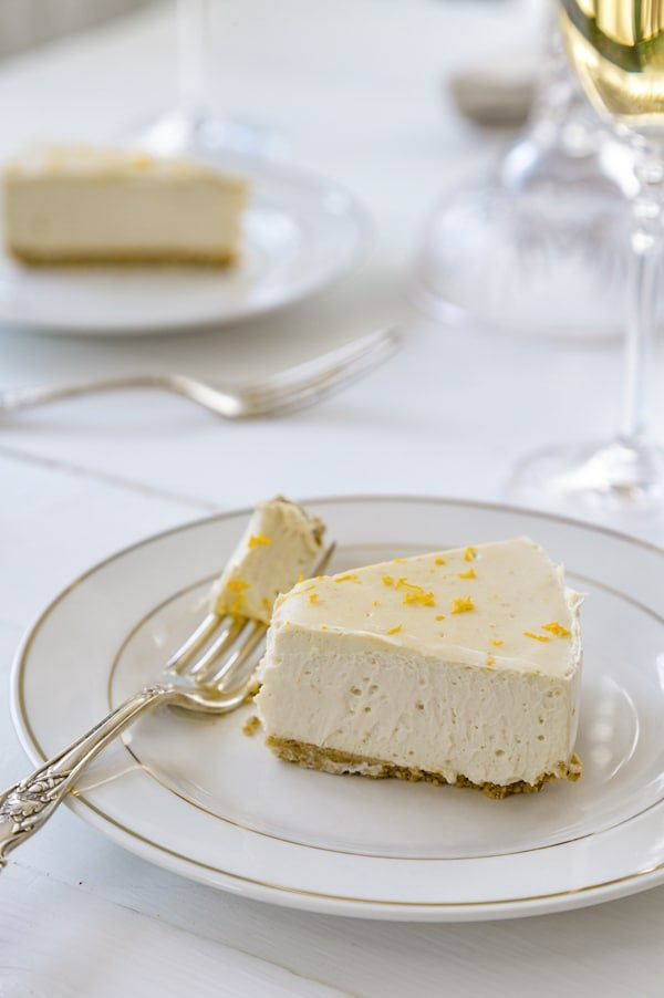 A slice of cheesecake with orange zest on a white plate with a silver fork full of the cake and a white plate and a glass of white wine in the background.