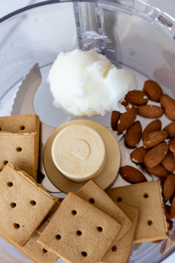 Graham crackers, almonds, and coconut oil in a food processor.