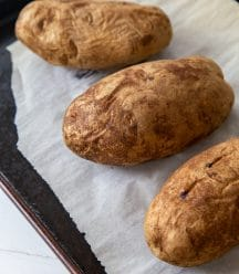 Three baked potatoes on a parchment lined baking sheet.