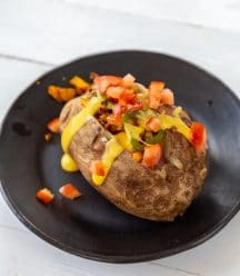 A baked potato on a black plate with cheese and tomatoes