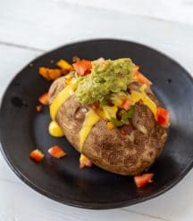 A stuffed baked potato on a black plate with tomatoes on the plate.