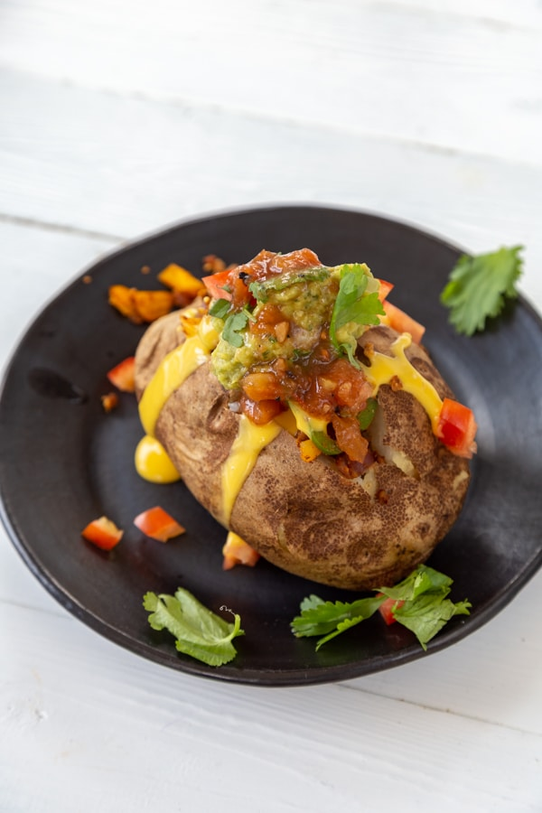 A stuffed baked potato on a black plate with cheese and topping falling down the sides.