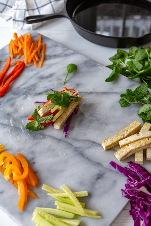 A spring roll wrapper on a marble board with vegetables and greens on top.