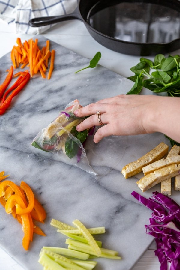 A hand rolling a spring roll with veggies on a marble board.