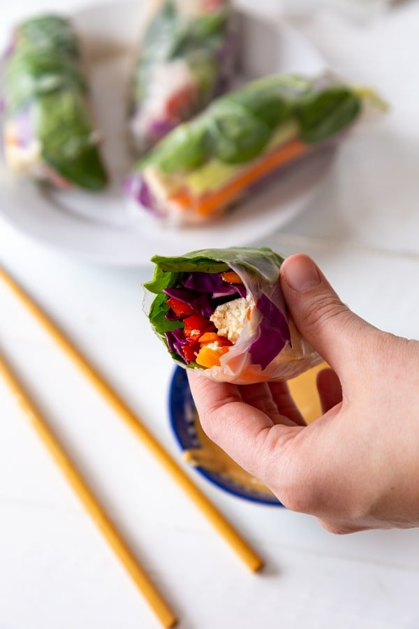 A hand holding a veggie spring roll and a white plate with 3 rolls and chopsticks on a white table.