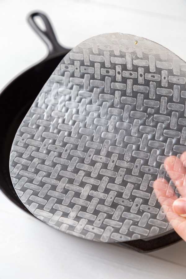 A round piece of rice paper being dipped into a pan of water.