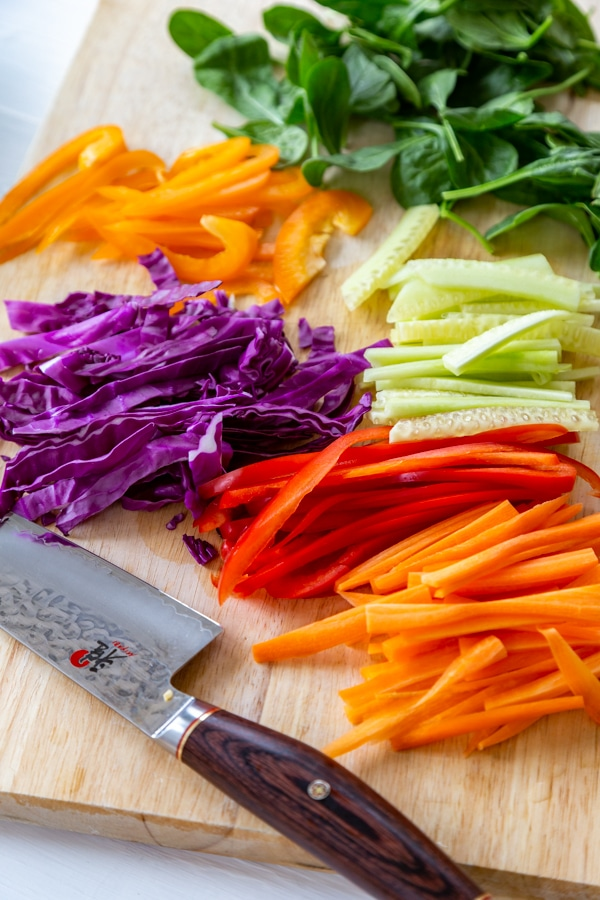 A cutting board and a knife with sliced bell peppers, red cabbage, cucumber, and carrots.
