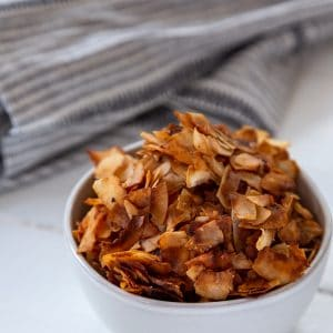 A white bowl filled with coconut bacon on a white table with a gray towel next to it.