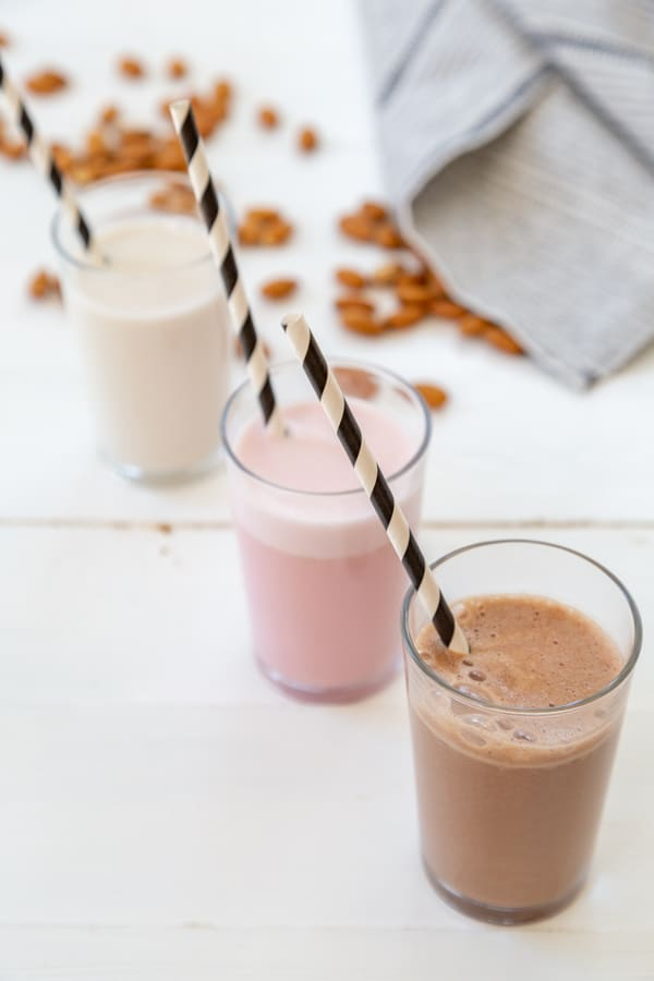 A glass of chocolate, strawberry, and plain almond milk in a row with black and white straws in the glasses and almonds scattered next to them on a white table.