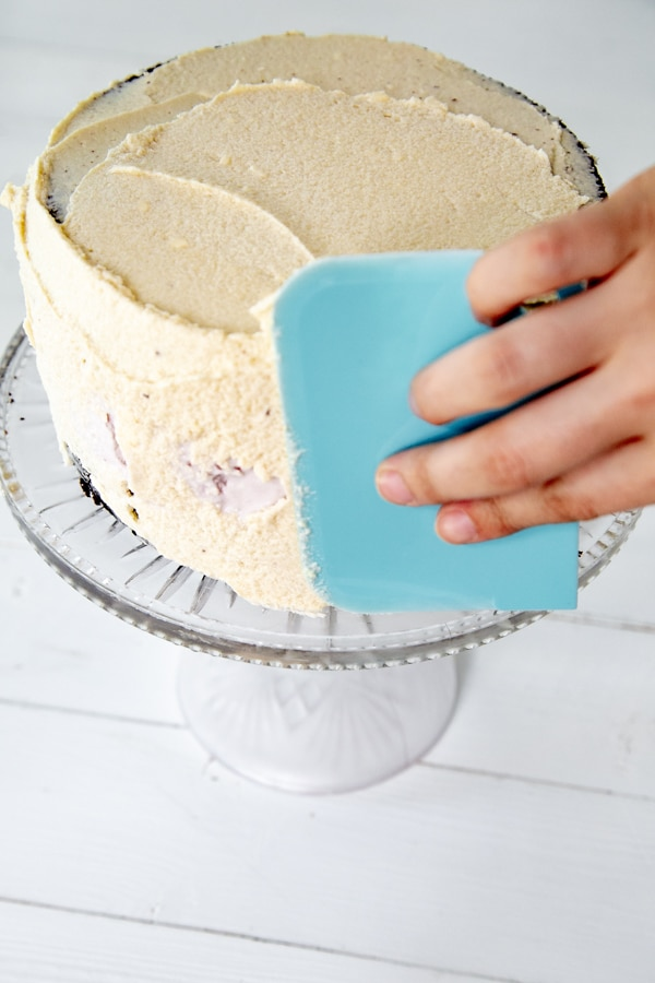 A hand spreading vanilla frosting on a cake with a blue cake scraper.