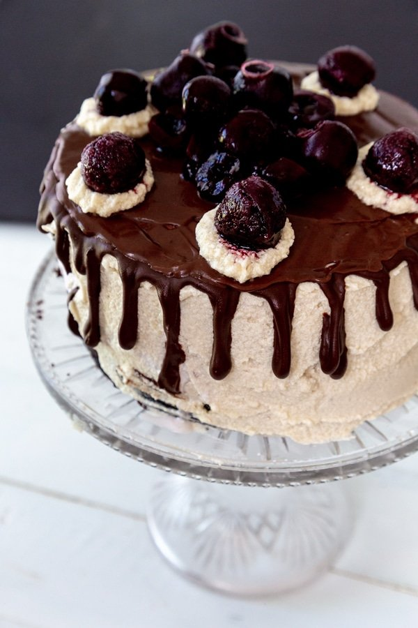 A cake with vanilla frosting, chocolate ganache dripping down the sides, and cherries on top.